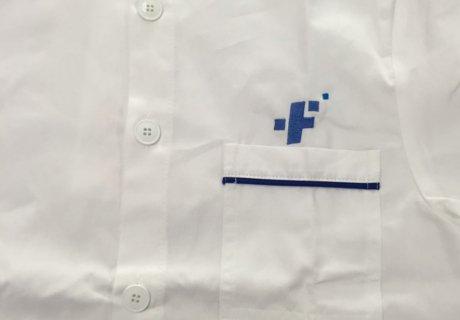 Logo en azul bordado sobre una bata blanca