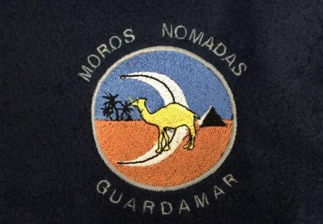 Logo comparsa en colores bordado junto a un camello en una sudadera negra.