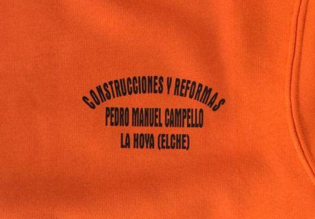Logo empresa de construcciones sobre camiseta naranja.