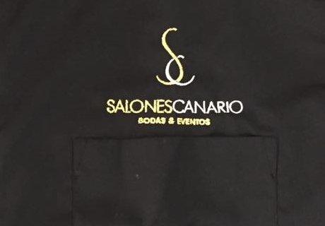 Logo restaurante en blanco y amarillo sobre camisa azul oscura