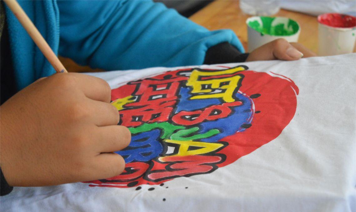 En la imagen podemos ver una mano dibujando con pintura sobre una camiseta