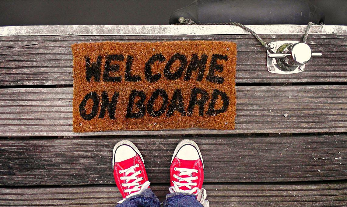 En la imagen podemos ver unas zapatillas rosas y una alfombra de bienvenida en la que pone 'Welcome on board'